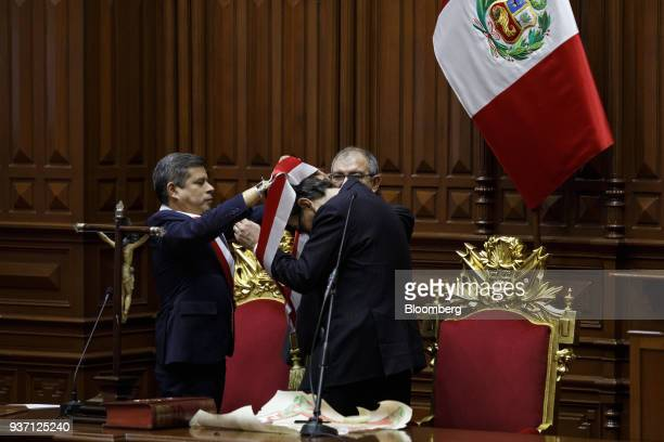 Congressman Luis Galarreta left places a sash around Martin Vizcarra Peru's president during a swearing in ceremony in Lima Peru on Friday March 23...