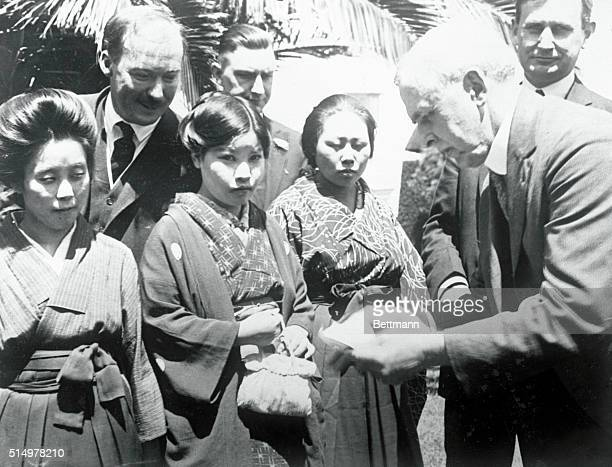 Congressman Raker looking over the passport of one of the Japanese picture brides at Angel Island the Ellis Island of the West Coast