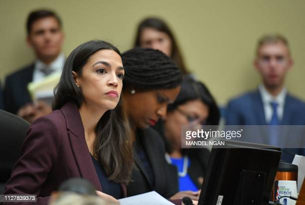 US Congresswoman Alexandria OcasioCortez listens as Michael Cohen attorney for President Trump testifies before the House Oversight and Reform...