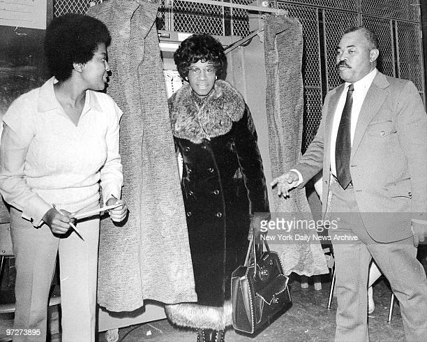 Congresswoman Shirley Chisholm looking out of voting booth at PS 289 in Brooklyn with her husband Conrad standing next to her