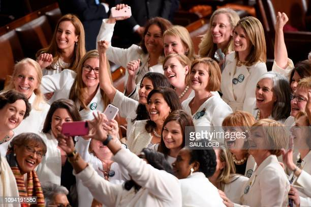 TOPSHOT Congresswomen dressed in white in tribute to the women's suffrage movement pose for a photo as they arrive for the State of the Union address...