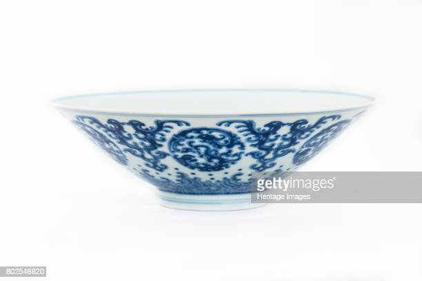 A conical bowl decorated in underglaze blue on the exterior with kui dragon medallions bordered by stylised doublebird patterns and stylised waves...