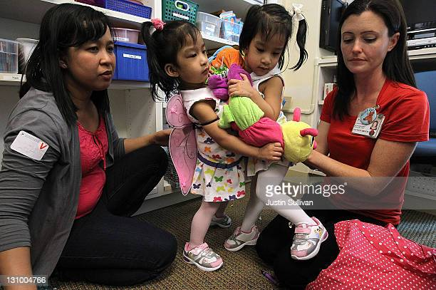 Conjoined twins Angelica and Angelina Sabuco their mother Ginady and child life specialist Allison Brooks during a press conference at the Lucile...