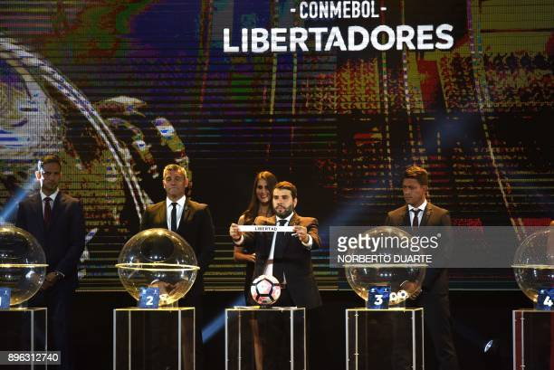 Conmebol competitions director Hugo Figueredo holds up a paper with the name of Paraguayan club Libertad during the Copa Libertadores 2018 draw at...