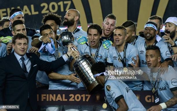 Conmebol President Alejandro Dominguez delivers the Copa Libertadores trophy to Brazil's Gremio captain Geromel during the award ceremony after...