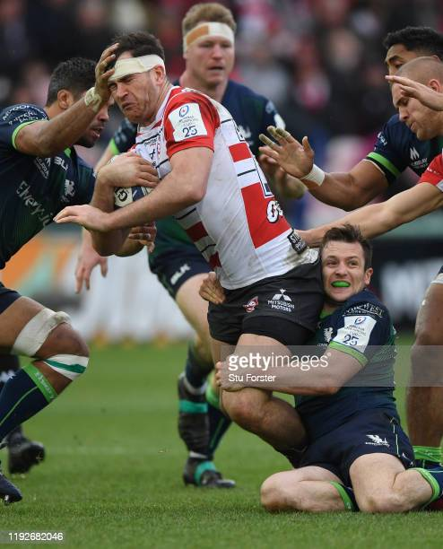 Connacht player Jack Carty hangs onto Gloucester centre Mark Atkinson during the Heineken Champions Cup Round 3 match between Gloucester Rugby and...