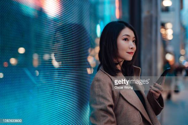 connect the future - young woman using mobile phone on street - communication stock pictures, royalty-free photos & images