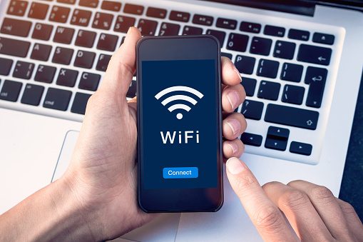 Connect to WiFi wireless internet network with smartphone at coffee shop or hotel with button on mobile device screen, free public hotspot secure access to web for email and website browsing 1146115827