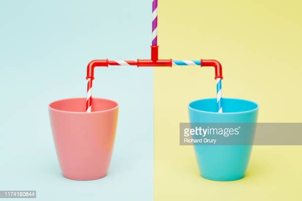 connected drinking straws in different two cups - man made object stock pictures, royalty-free photos & images