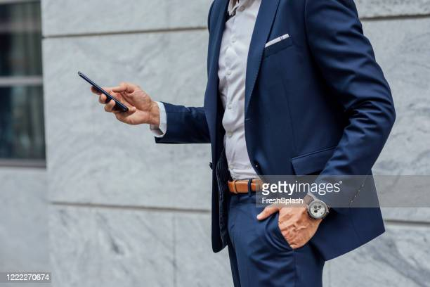 connected on the go: hands of an unrecognizable businessman using his mobile phone on the street - hands in pockets stock pictures, royalty-free photos & images