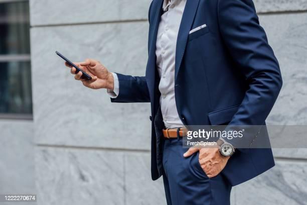 connesso in movimento: mani di un uomo d'affari irriconoscibile usando il suo telefono cellulare per strada - mani in tasca foto e immagini stock