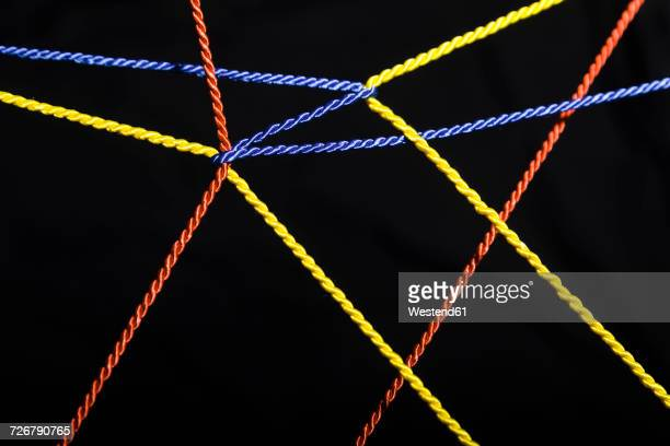 Connected ropes in front of black background