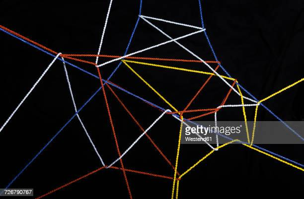 connected threads in front of black background - thread stock pictures, royalty-free photos & images