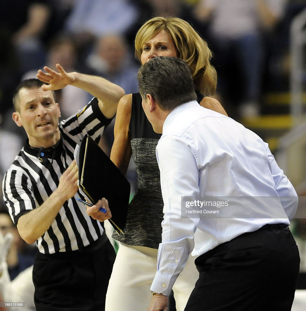 Connecticut associate head coach Chris Dailey does her best, in vain, to keep head coach Geno Auriemma from picking up a technical foul from official Joseph Vaszily late in the first half in a East Region Sweet 16 game against Maryland on Saturday, March 30, 2013, at the Webster Bank Arena at Harbor Yard in Bridgeport, Connecticut. UConn moved on, 76-50.