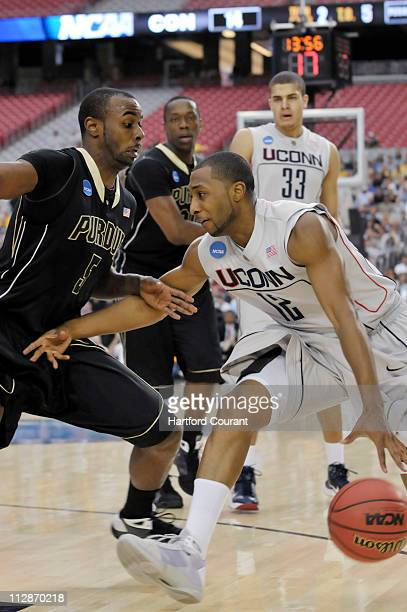 Connecticut guard AJ Price is guarded by Purdue guard Keaton Grant in the first half of an NCAA men's college basketball tournament game on Thursday...