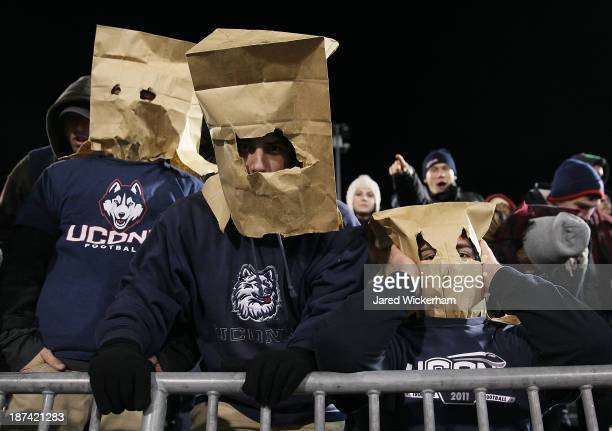 Connecticut Huskies fans wear bags on their heads in the second quarter against the Louisville Cardinals at Rentschler Field during the game on...