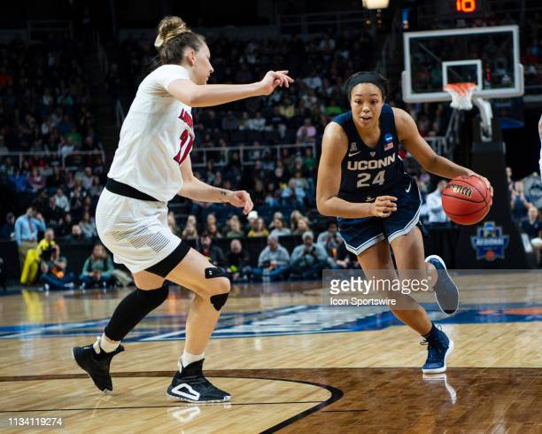 Connecticut Huskies Forward Napheesa Collier dribbles the ball down the lane with Louisville Cardinals Guard Arica Carter defending during the first...