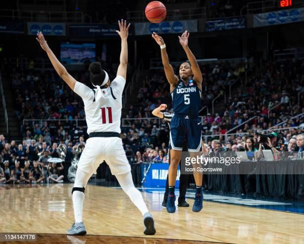 Connecticut Huskies Guard Crystal Dangerfield shoots a three point jump shot over Louisville Cardinals Guard Arica Carter defending during the first...