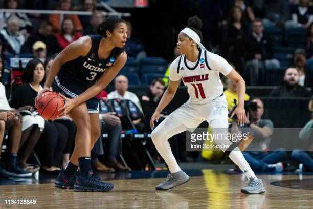 Connecticut Huskies Guard / Forward Megan Walker look to pass the ball with Louisville Cardinals Guard Arica Carter defending during the second half...