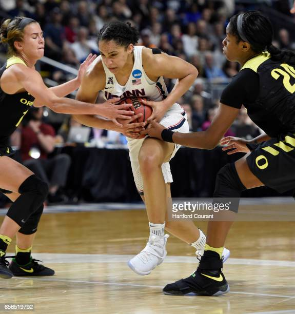 Connecticut Huskies guard Gabby Williams drives through Oregon Ducks guard Lexi Bando and forward Ruthy Hebard during the first half in the East...