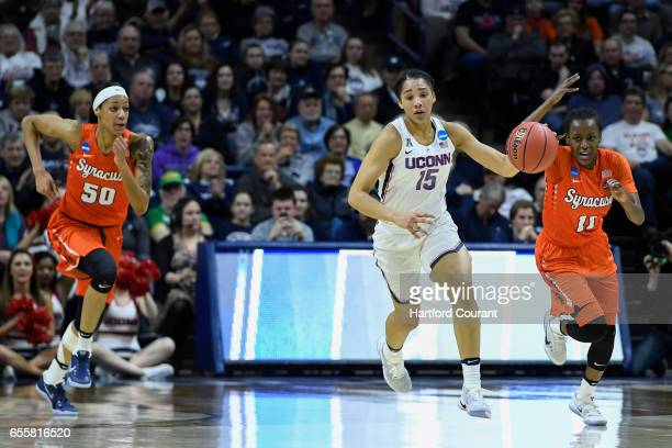 Connecticut Huskies guard Gabby Williams pushes the ball up court after grabbing a rebound against Syracuse Orange center Briana Day and Syracuse...