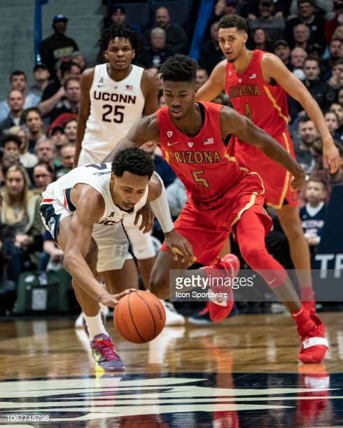 Connecticut Huskies guard Jalen Adams recovers a loose ball with Arizona Wildcats Guard Brandon Randolph defending during the second half of the...