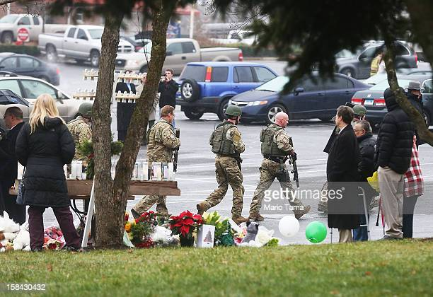 Connecticut State Police officers walk past a makeshift memorial to shooting victims while searching outside St Rose of Lima Roman Catholic Church...