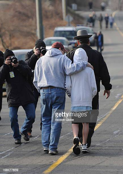 Connecticut state troopers escort a father and son through a media gauntlet to place flowers by a Sandy Hook Elementary sign on Dec. 15 one day after...