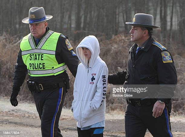 Connecticut state troopers escort an unidentified child as he tried to place flowers near Sandy Hook Elementary School on Dec. 15 one day after a...