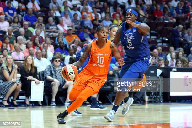 Connecticut Sun guard Courtney Williams drives past Minnesota Lynx forward Lynetta Kizer during the first half of a WNBA game between Minnesota Lynx...