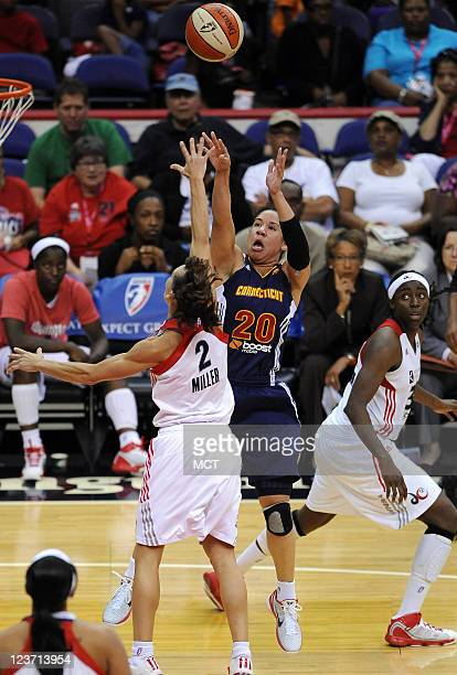 Connecticut Sun guard Kara Lawson shoots and scores over Washington Mystics guard Kelly Miller during the third quarter at the Verizon Center in...