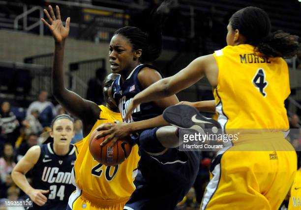 Connecticut's Brianna Banks grabs an offensive rebound in between Marquette's Apiew Ojulu and Arlesia Morse during the first half at the Al McGuire...