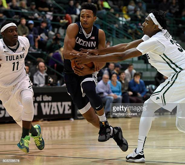 Connecticut's Jalen Adams protects the ball as he drives past Tulane's Melvin Frazier right and Kain Harris during the second half at Fogelman Arena...