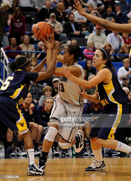 Connecticut's Maya Moore loses the ball while under pressure by West Virginia's Sarah Miles and Liz Repella in the Big East Tournament championship...
