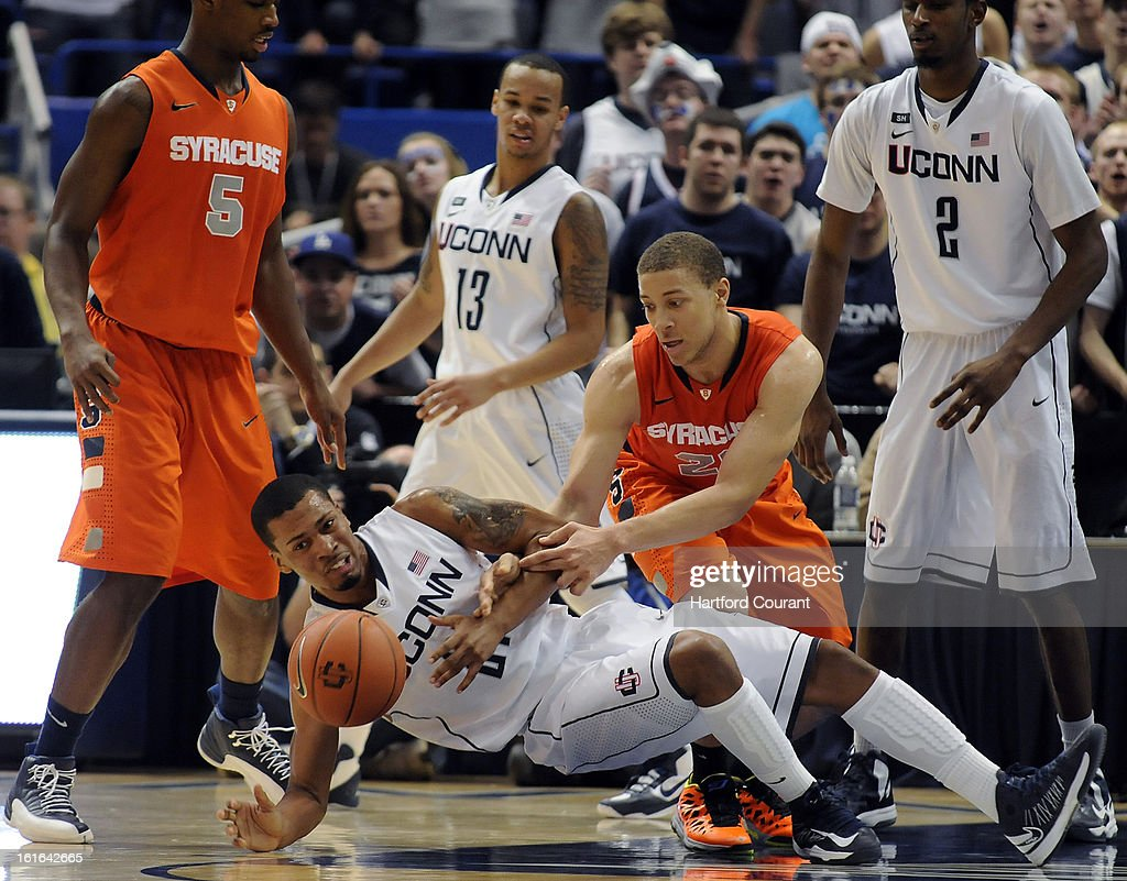 Connecticut's Omar Calhoun (21) is tangled up with Syracuse's Brandon Triche (20) as they battle for a lose ball during the second half on Wednesday, February 13, 2013, at the XL Center in Hartford, Connecticut. UConn defeated Syracuse, 66-58.