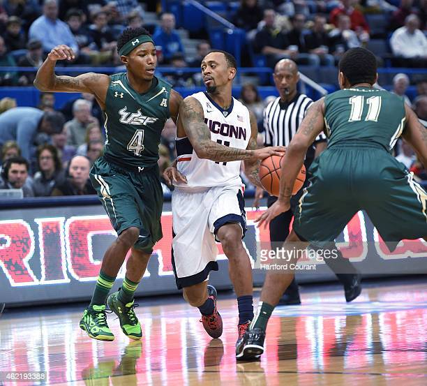 Connecticut's Ryan Boatright looks to pass around the defense of South Florida's Corey Allen Jr and Anthony Collins in the second half at the XL...