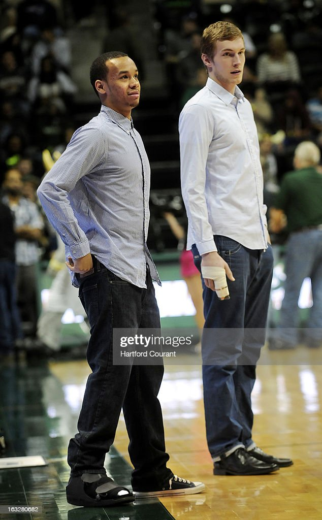 Connecticut's Shabazz Napier, left, in street clothes with a foot injury, and Niels Giffey, out with a fractured finger, on the sidelines during warm-ups against South Florida at the USF Sun Dome in Tampa, Florida, on Wednesday, March 6, 2013. USF won, 65-51.