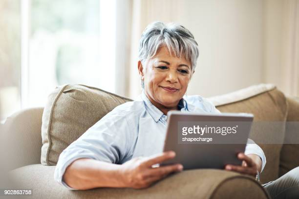 connecting at home in her retirement - using digital tablet stock pictures, royalty-free photos & images