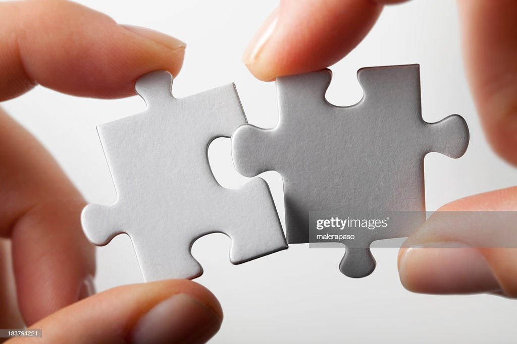 Connection. Hands trying to fit two puzzle pieces together. : Stock Photo