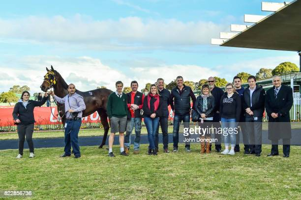 Connections pose with Intrigo after winning the Christmas in July @ Highways Handicap at Ladbrokes Park Hillside Racecourse on July 26 2017 in...