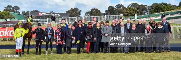 Connections pose with jockey Craig Williams and Peruggia after winning the Chandler Macleod Handicap at Ladbrokes Park Hillside Racecourse on July 26...