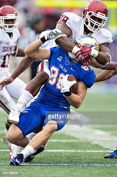 Conner Floyd of the Tulsa Golden Hurricanes is tackled by Eric Striker of the Oklahoma Sooners at HA Chapman Stadium on September 6 2014 in Tulsa...