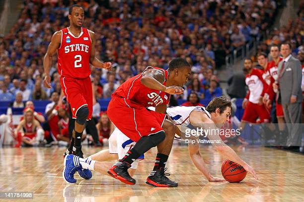Conner Teahan of the Kansas Jayhawks dives for a loose ball in the first half against Alex Johnson of the North Carolina State Wolfpack during the...