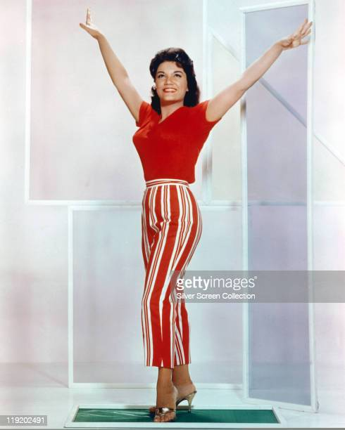 Connie Francis US pop singer waring redandwhite striped trousers and a red tshirt with her arms outstretched either side of her in a studio portrait...