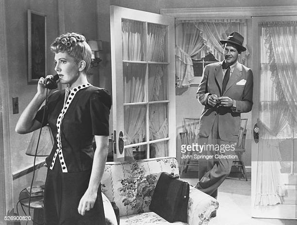 Connie Milligan talks on the phone while Joe Carter looks on in a scene from the 1943 film The More the Merrier