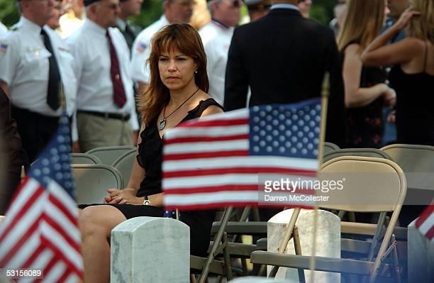 Connie Piper sits beside the grave of her husband, Army Staff Sgt. Christopher Piper June 27, 2005 during his funeral in Marblehead, Massachusetts....
