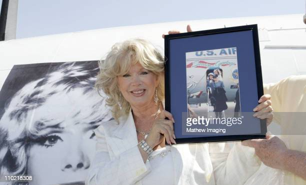 Connie Stevens poses with a Special Painted Lockheed Constellation picturing herself and holds a Dedicated past USO tour photo.