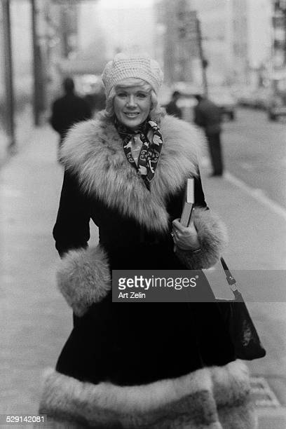 Connie Stevens wearing a fur trimmed coat walking on the street circa 1970 New York