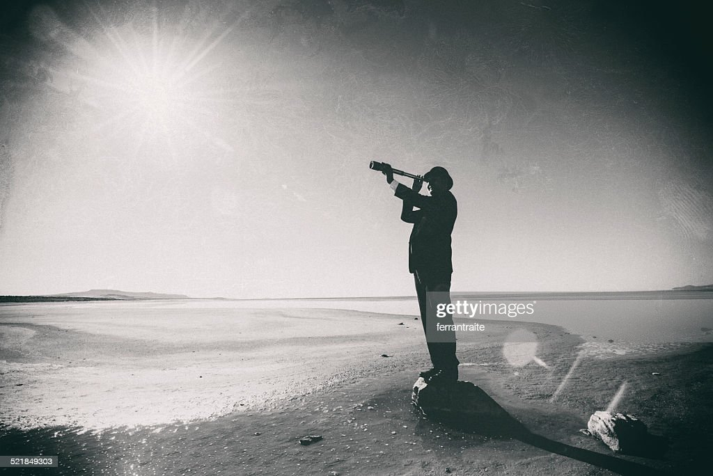 Connoisseur looks through spyglass in the dessert : Stock Photo