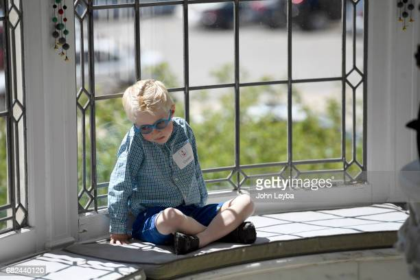 Connor Batal 5yearsold has a quiet moment sitting into e window seal at the Governor's Mansion during an event for the Anchor Center for the blind...